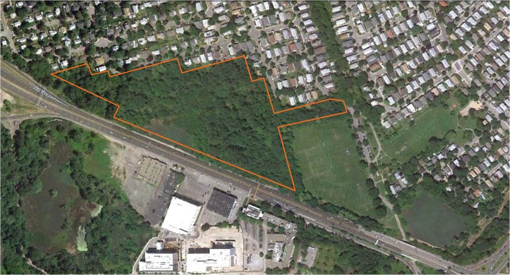The Mugar parcel, outlined in white, abuts Route 2 (center). This 2011 aerial photo also depicts the former Faces site and parking lot (bottom), now the location of the Vox on 2 apartments. / Arlington Land Trust